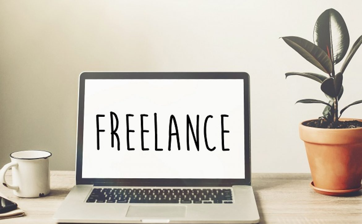 Freelance text on laptop screen on wooden desktop with phone, notebook, coffee and plant. space for text. business workspace in home or office. internet working concept